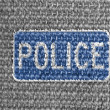 Police road sign painted on grey fabric - Stock Photo