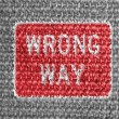 Wrong way road sign painted on grey fabric — Stock Photo
