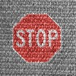 Stop road sign painted on grey fabric — Stock Photo