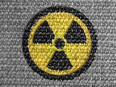 Nuclear radiation symbol painted on grey fabric — Stock Photo