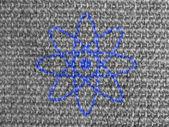 Atom symbol painted on grey fabric — Stock Photo