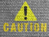 Caution sign painted on grey fabric — Stock Photo