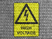 High voltage sign drawn at grey fabric — Stock Photo