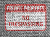No trespassing sign painted on grey fabric — Stock Photo