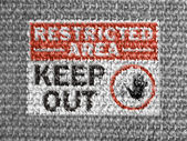 Restricted area sign painted on grey fabric — Stock Photo
