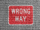 Wrong way road sign painted on grey fabric — Foto de Stock