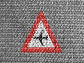 Low flying aircraft or sudden aircraft noise road sign painted on grey fabric — Stock Photo