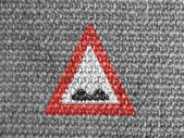 Uneven road sign painted on grey fabric — Stock Photo