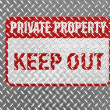 Keep out sign painted on metal floor - Stock Photo