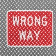 Stock Photo: Wrong way road sign painted on metal floor