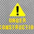 Under construction caption painted on metal floor — Stock Photo #15368281