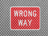 Wrong way road sign painted on metal floor — Stok fotoğraf