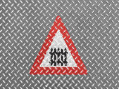 Level crossing with barrier or gate ahead road sign painted on metal floor — Stock Photo