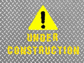 Under construction caption painted on metal floor — Stock Photo