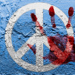 Peace symbol painted on grunge wall with bloody palmprint over it — Stock Photo #15376157
