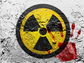 Nuclear radiation symbol painted on grunge wall with bloody palmprint over it — Stock Photo