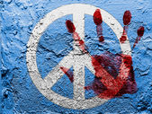 Peace symbol painted on grunge wall with bloody palmprint over it — ストック写真