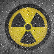 Stock Photo: Nuclear radiation symbol painted on metal surface covered with rain drops