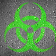 Biohazard sign painted on metal surface covered with rain drops - Stock Photo
