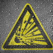 Explosive sign drawn on metal surface covered with rain drops - Stock Photo