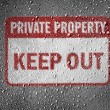 Keep out sign painted on metal surface covered with rain drops - Stock Photo