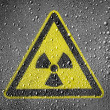 Nuclear radiation sign drawn on metal surface covered with rain drops - Stock Photo