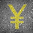 Yen sign painted on metal surface covered with rain drops — Stock Photo