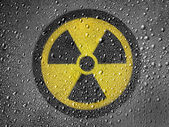 Nuclear radiation symbol painted on metal surface covered with rain drops — Stock Photo