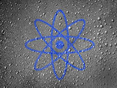 Atom symbol painted on metal surface covered with rain drops — Stock Photo
