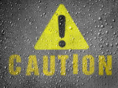 Caution sign painted on metal surface covered with rain drops — Stock Photo