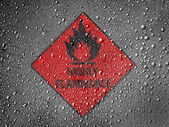Highly flammable sign drawn on metal surface covered with rain drops — Stock Photo