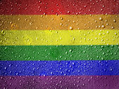 Gay pride flag painted on metal surface covered with rain drops — Stock fotografie