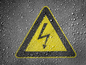 Electric shock sign painted on metal surface covered with rain drops — Stock Photo