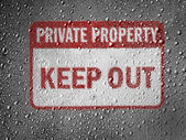 Keep out sign painted on metal surface covered with rain drops — Stock Photo