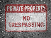 No trespassing sign painted on metal surface covered with rain drops — Stock Photo