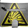Explosive sign drawn on crocodile skin purse - Stock Photo
