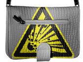 Explosive sign drawn on crocodile skin purse — Stock Photo