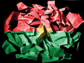 Burkina Faso flag painted on pieces of torn paper on black background — Stock Photo