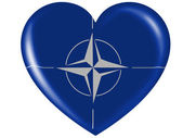 NATO symbol painted on painted on glossy heart icon — Stock Photo