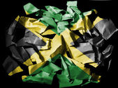 Jamaica flag painted on pieces of torn paper on black background — Stok fotoğraf