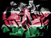 Kenya flag painted on pieces of torn paper on black background — Stock Photo