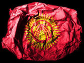 Kyrgyzstan flag painted on crumpled paper on black background — Stock Photo