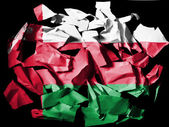 Oman flag painted on pieces of torn paper on black background — Stock Photo