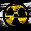 Stock Photo: Nuclear radiation symbol painted on black textured paper with watercolor