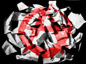 Anarchy symbol painted on pieces of torn paper on black background — Stock Photo