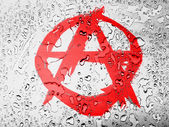 Anarchy symbol painted on covered with water drops — Stock Photo