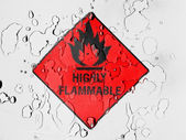 Highly flammable sign drawn on covered with water drops — Stock Photo