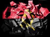 Angola. drapeau angolais peintes sur des morceaux de papier déchiré sur fond noir — Photo