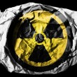 Nuclear radiation symbol painted on painted on crumpled paper on black background — Stock Photo #23435692