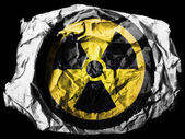 Nuclear radiation symbol painted on painted on crumpled paper on black background — Stock Photo